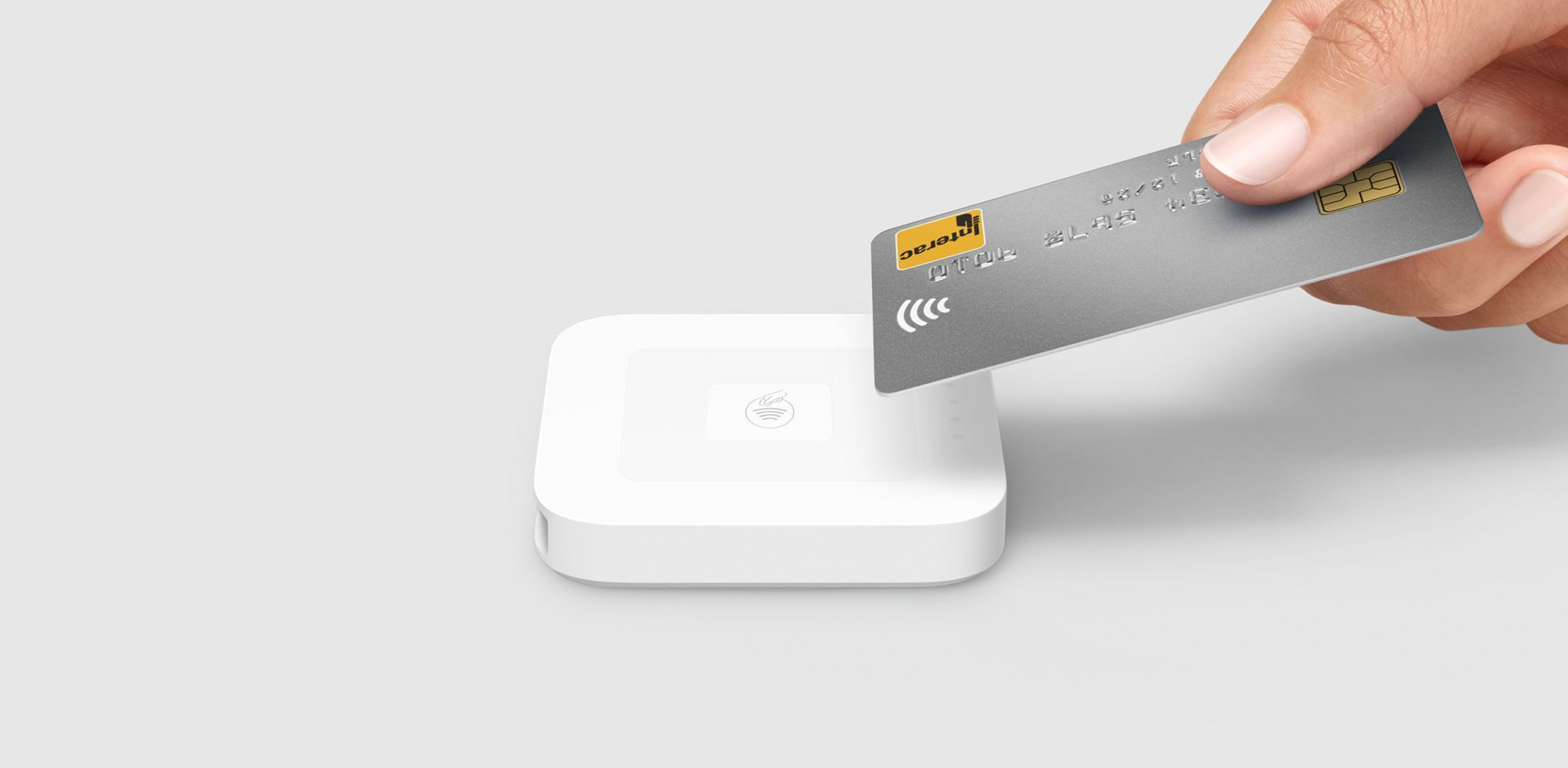 Main tenant un téléphone affichant Apple Pay et un Square Reader